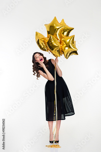 Amusing cheerful lovely curly girl  holding golden balloons Poster