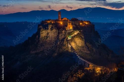 Foto op Aluminium Nachtblauw Panorama con vista di Civita di Bagnoregio arroccata sul cucuzzolo all'alba