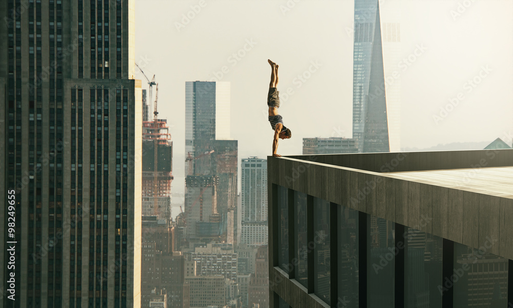 Fototapeta Man performs a handstand on the edge of a skyscraper