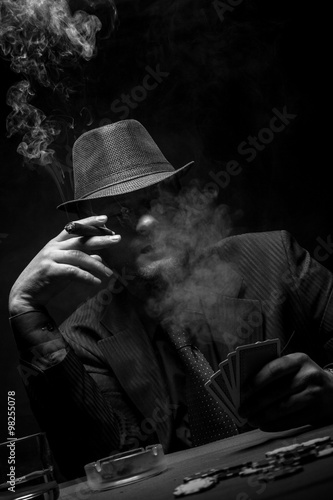 Fototapeta  Male gambler playing poker, drinking whiskey and smokes a cigar, Black and white