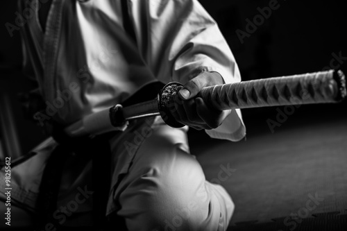 Papiers peints Combat Close up of young martial arts fighter with katana siting in seiza position, black and white.