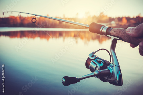 Foto auf AluDibond Fischerei hand with spinning and reel on the evening summer lake