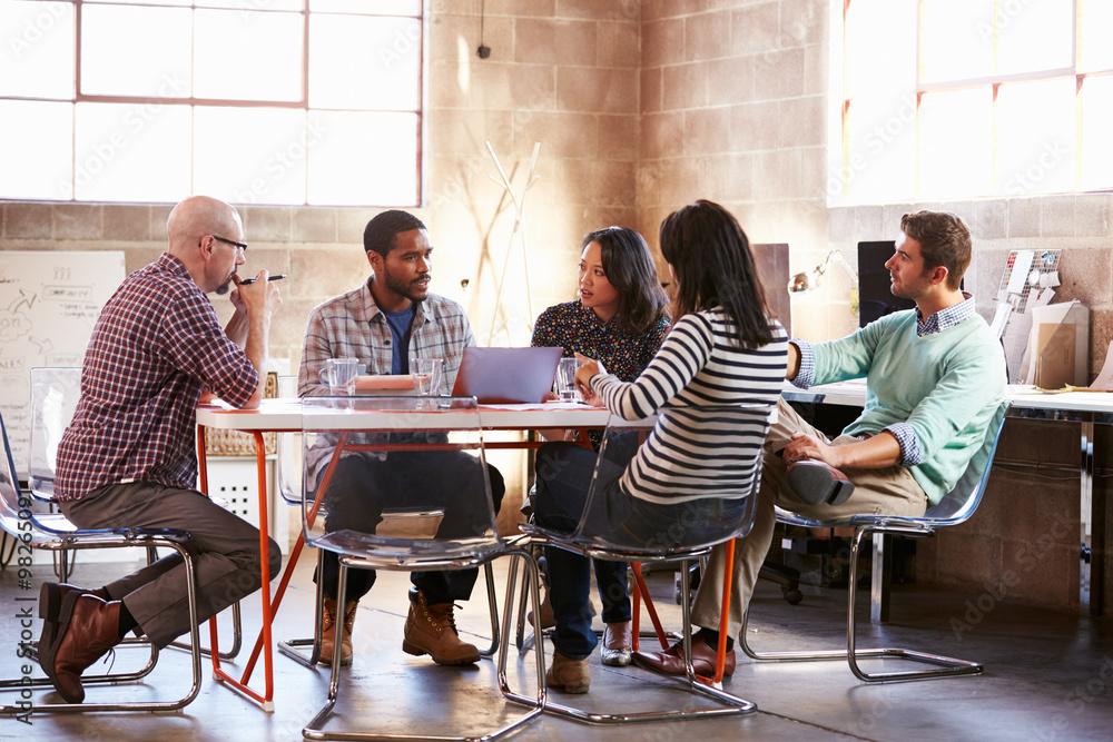 Fototapeta Group Of Designers Having Meeting Around Table In Office