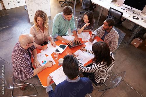 Overhead View Of Designers Having Meeting Around Table Wallpaper Mural
