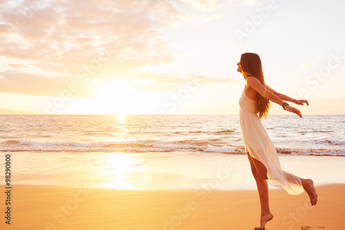 Fotografia  Happy Carefree Woman Dancing on the Beach at Sunset