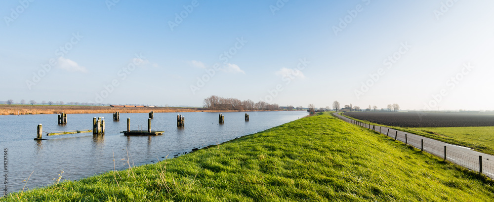 Fototapeta Grassy dike along a canal with wooden bollards