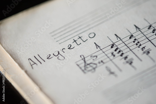 Photo Musical tempo Allegretto in a music book with hand-written notes