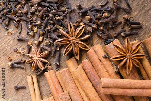 Fototapeta laski cynamonu, gwiazdki anyżu i goździki na drewnianym blacie obraz