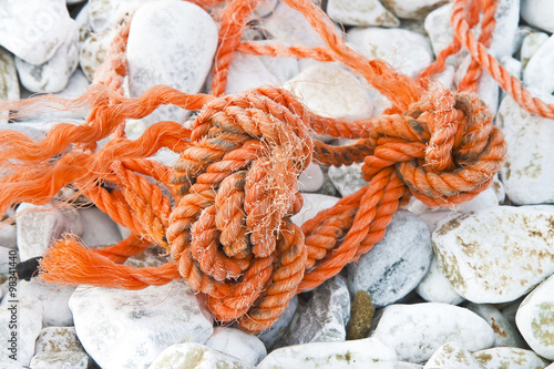 Fotografie, Obraz  Old damaged tangled plastic rope abandoned on the ground