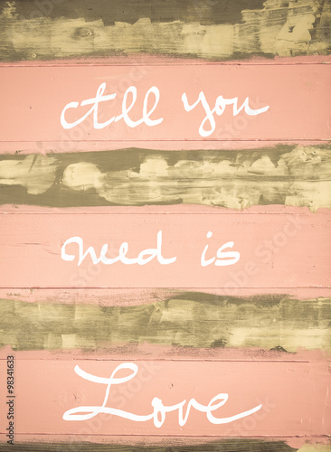Photo  Concept image of All You need is love motivational quote hand written on vintage