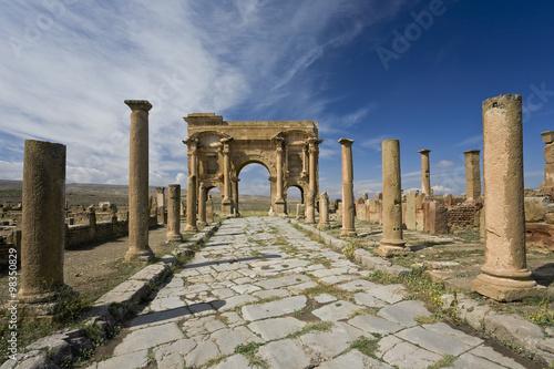Staande foto Algerije Algeria. Timgad (ancient Thamugadi or Thamugas). Decumanus street and surrounding colonnade terminated Trajan's Arch