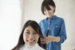 Hairdresser is trying to cut the long hair of women