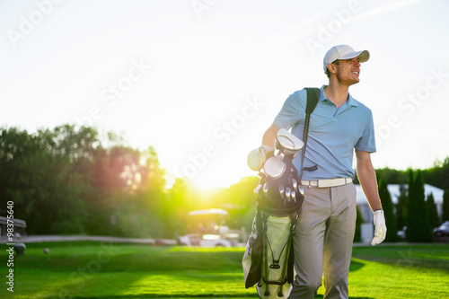 Poster Golf Young man with a golf bag outdoors