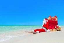 Christmas Santa Claus With Sack Of Gift Boxes At Beach