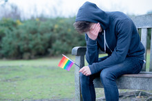Depressed Teenage Boy Holding A Pride Flag