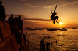 Silhouette of Happy Young boy jumping in water at sunset in Zanz