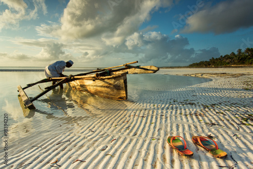 Tuinposter Zanzibar Traditional fisher boat in Zanzibar with people going to fish on