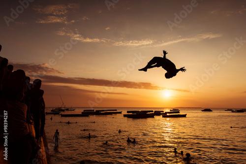 Printed kitchen splashbacks Zanzibar Silhouette of Happy Young boy jumping in water at sunset in Zanz