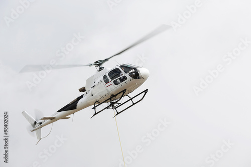 Tuinposter Helicopter white flying helicopter transporting cargo in the Dolomites, the