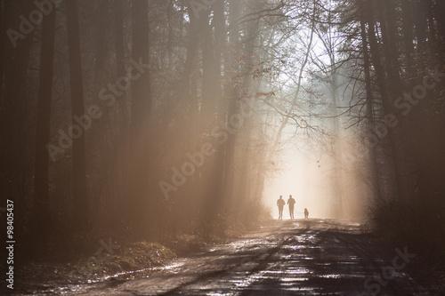 Tuinposter Weg in bos Biegająca para ludzi z psem w mglistym lesie