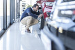 Man examining new car at car dealership