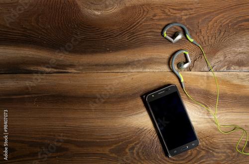 Obraz Telefon i słuchawki na drewnianym tle - fototapety do salonu