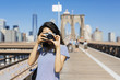 USA, New York City, young woman standing on Brooklyn Bridge taking a photo with camera