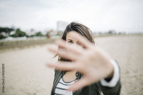 Spain, Tarragona, young woman looking through her outstretched hand