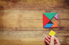 Top View Photo Of Man's Hand Holding A Missing Piece In A Square Tangram Puzzle, Over Wooden Table.