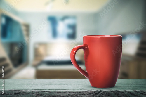 Red cup with hot drink on the table (vintage toning)
