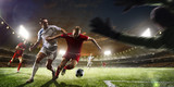 Fototapeta sport - Soccer players in action on sunset stadium background panorama