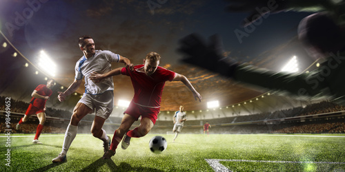 Obraz Soccer players in action on sunset stadium background panorama - fototapety do salonu