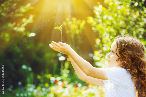 Fotografie, Obraz  Cute girl holding young green plant in sunlight.