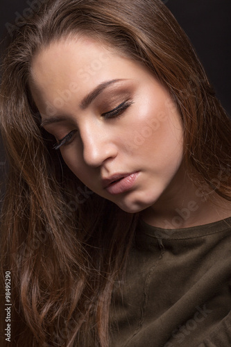 Valokuva  Portrait of the girl with closed eyes on a black background, gre