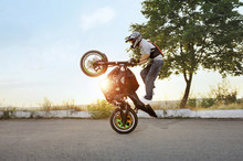 Living On The Edge. Extreme Stunt Driver Standing On His Bike In A Stunt Soft Smudged Focus