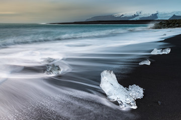 FototapetaIce cube with smooth wave at black sand beach Iceland during sunrise