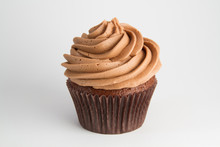A Chocolate Cupcake With Swirled Frosting On A White Background.