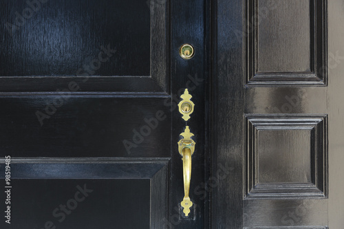 Fotografie, Obraz  front door, close up of black front door with brass handle
