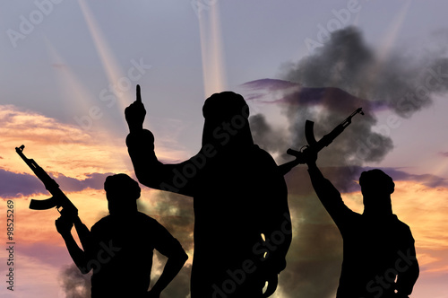 Fotomural Silhouette of men with rifles against cloudy sky during sunset
