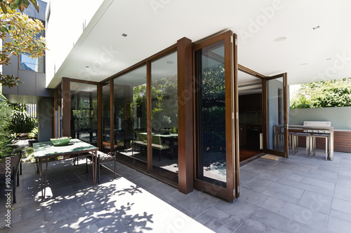 Canvas Bi fold doors opening to rear courtyard of contemporary home