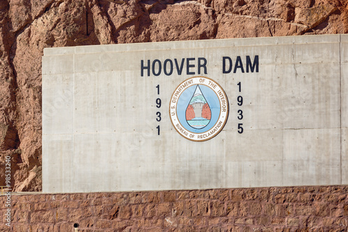 Fotografia  Sign at entrance to Hoover Dam on the concrete wall on red rocks backgroud