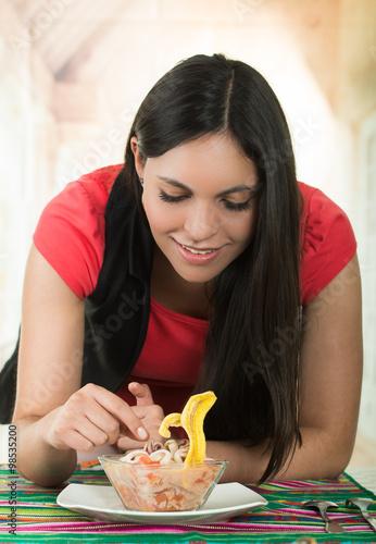 Deurstickers Kruidenierswinkel Beautiful young brunette girl enjoying a seafood cebiche