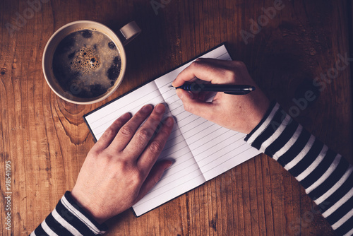 Valokuva  Woman drinking coffee and writing a diary note