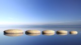Fototapeta Kamienie - Zen stones row from large to small  in water with blue sky and peaceful landscape background