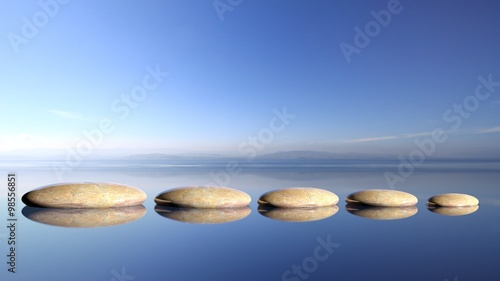 Zen stones row from large to small  in water with blue sky and peaceful landscape background - 98556851