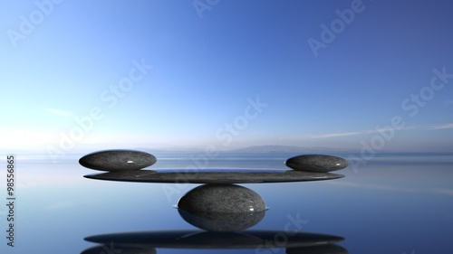 Balancing Zen stones in water with blue sky and peaceful landscape. - 98556865