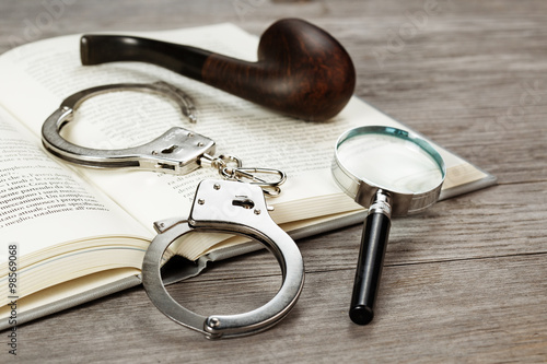 Fotografia  handcuffs, magnifying glass and pipe on book