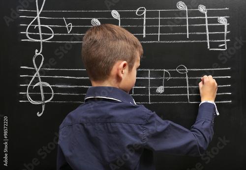 Fotografía  El muchacho lindo por escrito en la pizarra con las notas musicales, en el aula