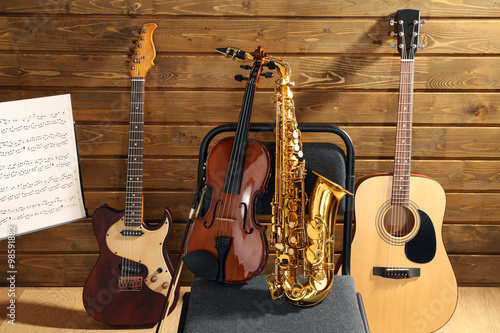 Fotografiet  Musical instruments on a chair and note holder against wooden background