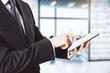 Businessman using digital tablet in light office